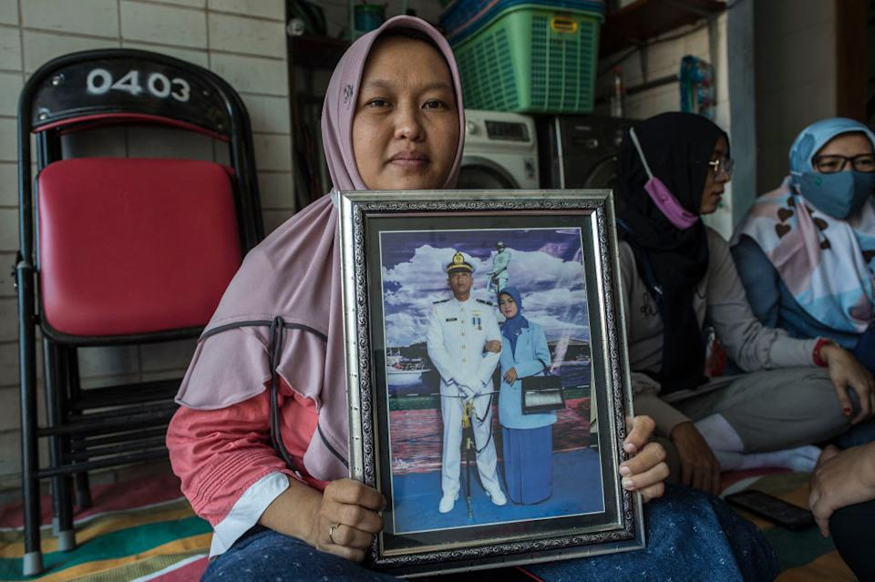 Ceci Yuemi poses with a photo of her husband, Second Lieutenant Munawir, who served on board the submarine KRI Nanggala 402, at a religious gathering in Surabaya.