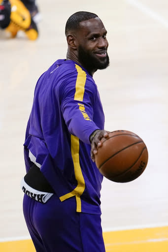 Los Angeles Lakers forward LeBron James points to a person in the stands before the team's NBA basketball game against the New Orleans Pelicans on Friday, Jan. 15, 2021, in Los Angeles. (AP Photo/Ashley Landis)