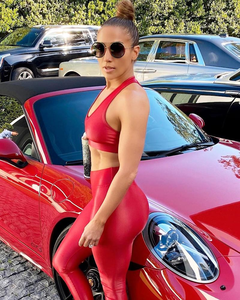 Jennifer Lopez poses in a sports bra and leggings by a car