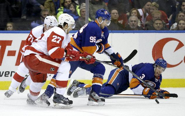 New York Islanders center Pierre-Marc Bouchard (96) and defenseman Travis Hamonic (3) battle for the puck with Detroit Red Wings defenseman Kyle Quincey (27) and right wing Daniel Cleary (71) during the second period of an NHL hockey game, Friday, Nov. 29, 2013, in Uniondale, N.Y. (AP Photo/Julio Cortez)