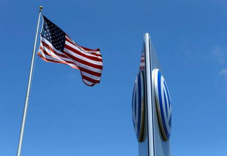 FILE PHOTO: A U.S. flag flutters in the wind above a Volkswagen automobile dealership in Carlsbad, California