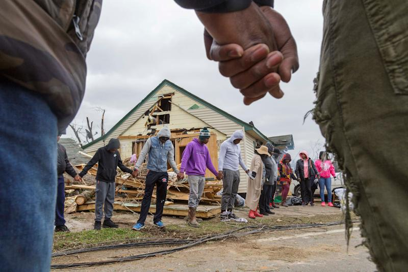 Residents of Talbotton, Ga. pray together outside a home destroyed by a tornado the day after storms battered Alabama and Georgia, March 4, 2019. (Photo: Grant Blankenship /The Macon Telegraph via AP)