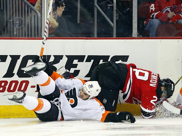 CORRECTS DAY OF WEEK FROM TUESDAY TO SATURDAY - Philadelphia Flyers' Zac Rinaldo, left, collides with New Jersey Devils' Anton Volchenkov, of Russia, as they fight for the puck during the first period of an NHL hockey game in Newark, N.J., Satuday, Nov. 2, 2013. (AP Photo/Rich Schultz)
