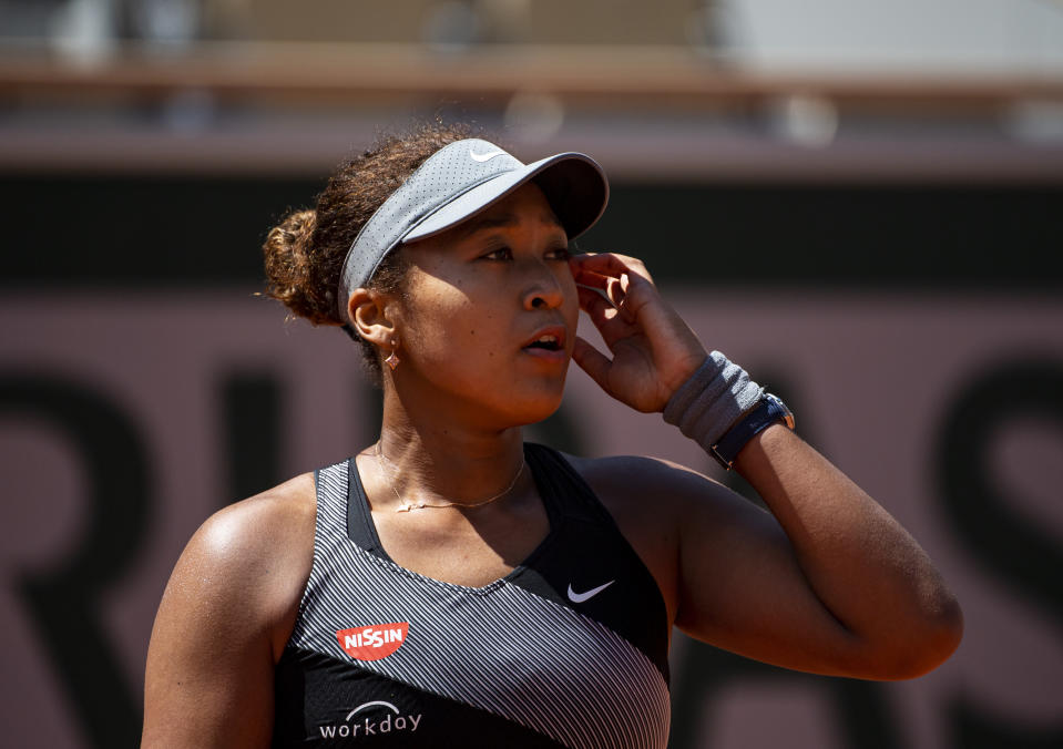 PARIS, FRANCE - MAY 30: Naomi Osaka of Japan looks to her team during her match against Patricia Maria Țig of Romania in the first round of the women's singles at Roland Garros on May 30, 2021 in Paris, France.