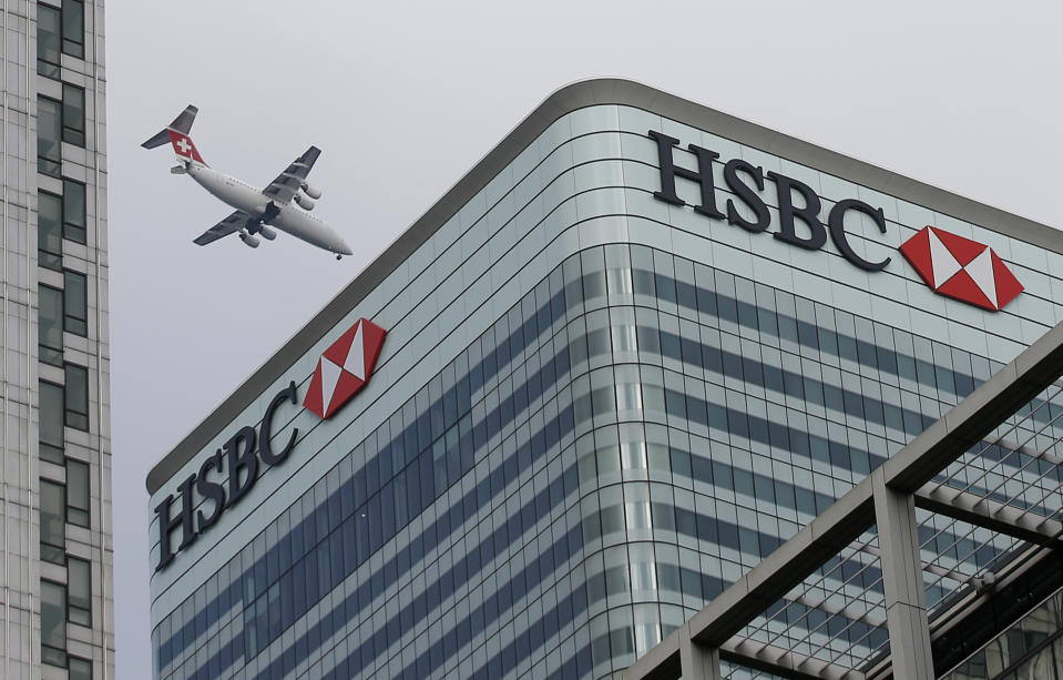 A Swiss International aircraft flies past the HSBC headquarters building in the Canary Wharf financial district in east London February 15, 2015. HSBC apologised to customers and investors on Sunday for past practices at its Swiss private bank after allegations that it helped hundreds of clients to dodge taxes. REUTERS/Peter Nicholls (BRITAIN - Tags: BUSINESS CRIME LAW TRANSPORT TPX IMAGES OF THE DAY)