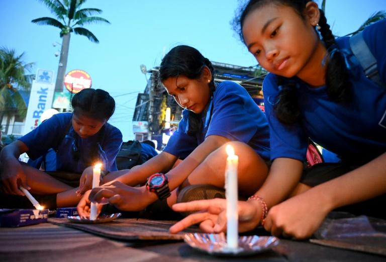 School children light candles during a memorial service to commemorate the 2002 Bali bombings which killed 202 people, most of them foreign tourists