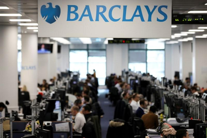 FILE PHOTO: Traders work on the trading floor of Barclays Bank at Canary Wharf in London, Britain