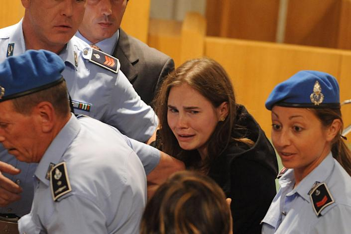 Amanda Knox cries after hearing the verdict that overturns her conviction and acquits her of murdering her British roomate Meredith Kercher, at the Perugia court, Italy, Monday Oct. 3, 2011. An Italian appeals court has thrown out Amanda Knox's murder conviction and ordered the young American freed after nearly four years in prison for the death of her British roommate. Knox collapsed in tears after the verdict was read out Monday. Her co-defendant, Raffaele Sollecito, also was cleared of killing 21-year-old Meredith Kercher in 2007. (AP Photo/Tiziana, Pool)