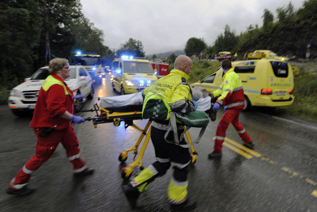 Medics and emergency workers escort an injured person from a camp site on the island of Utoya, Norway Saturday July 23, 2011. A Norwegian dressed as a police officer gunned down at least 84 people at an island retreat, police said Saturday. Investigators are still searching the surrounding waters, where people fled the attack, which followed an explosion in nearby Oslo that killed seven. (AP Photo/Morten Edvardsen/Scanpix) NORWAY OUT