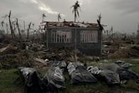 The bodies of five victims of typhoon Haiyan lie in front of a damaged house in Tanauan on November 20, 2013 in the Philippines