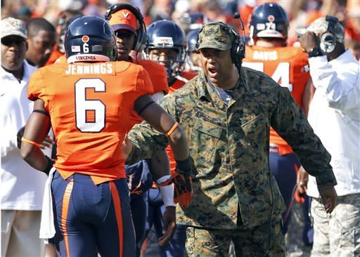 Virginia head coach Mike London, right, celebrates a touchdown with wide receiver Darius Jennings (6) during the first half of an NCAA college football game against Miami in Charlottesville, Va., Saturday, Nov. 10, 2012. (AP Photo/Steve Helber)