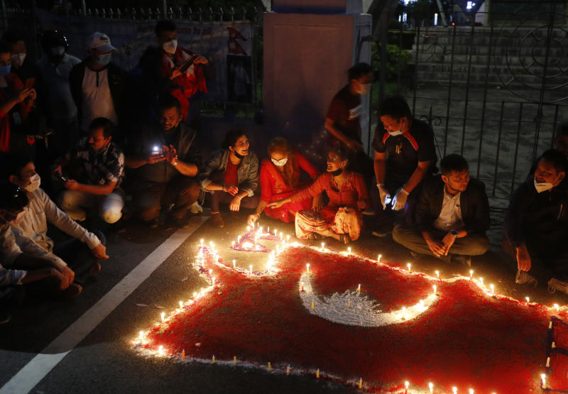 People light candles on an outline of the new map of Nepal drawn on a road as they celebrate the approval of the political map to include territory claimed by both India and Nepal, in Kathmandu, Nepal, Saturday, June 13, 2020. Nepal's Parliament on Saturday overwhelmingly approved the constitutional amendment to change the nation's political map. The voting follows the government's issuing of a new map last month that showed the disputed territory within its borders. (AP Photo/Niranjan Shrestha)