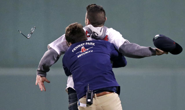 A Fenway Park security worker took down a fan who ran onto the field during the fifth inning of a baseball game Wednesday night. (AP)