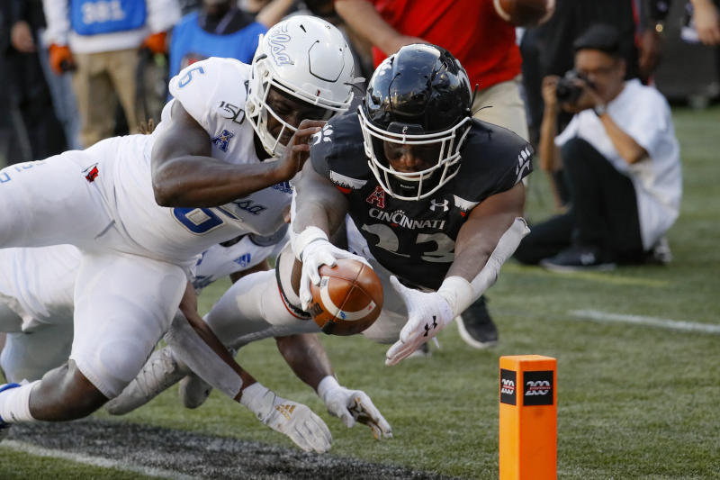 Cincinnati running back Gerrid Doaks (23) scores a touchdown against Tulsa linebacker Diamon Cannon (6) during the second half of an NCAA college football game, Saturday, Oct. 19, 2019, in Cincinnati. (AP Photo/John Minchillo)