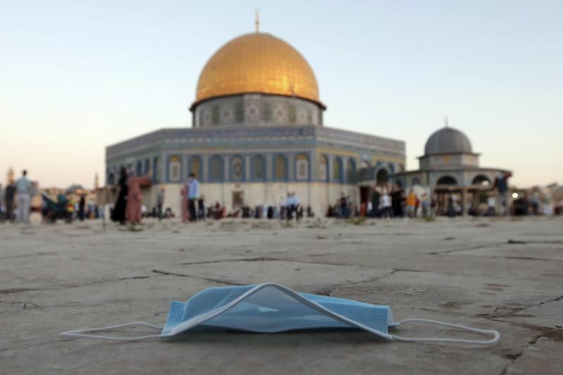 A protective face mask is thrown on the ground during Eid al-Adha prayer, next to the Dome of the Rock Mosque in the Al Aqsa Mosque compound in Jerusalem's old city, Friday, July 31, 2020. This is the first Feast of Sacrifice since the onset of the global coronavirus pandemic. Muslims worldwide marked the the Eid al-Adha holiday over the past days amid a global pandemic that has impacted nearly every aspect of this year's celebrations. (AP Photo/Mahmoud Illean)
