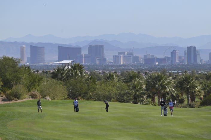 Robert Streb, center, takes his second shot on the eighth hole during first round of the CJ Cup golf tournament, Thursday, Oct. 14, 2021, in Las Vegas. (AP Photo/David Becker)