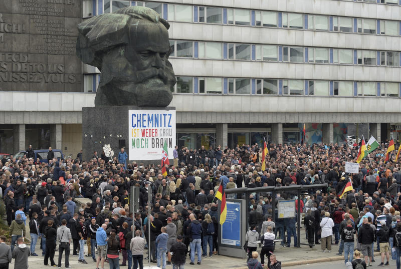 People gather around the Karl Marx statue in Chemnitz, eastern Germany, Saturday, Sept. 1, 2018, after several nationalist groups called for marches protesting the killing of a German man last week, allegedly by migrants from Syria and Iraq. (AP Photo/Jens Meyer)