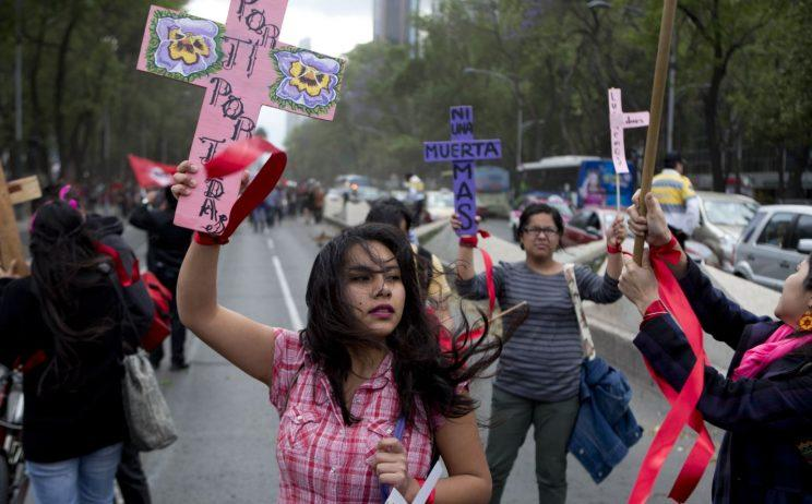 A woman carries a cross that reads in Spanish
