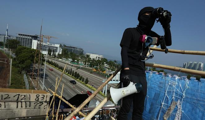 An anti-government protester keeps watch as Tolo Highway, near Chinese University, partially reopens. It was later shut down again. Photo: Jonathan Wong