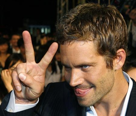 """U.S. actor Walker gestures to a fan during the premiere of the movie """"Fast and Furious 4"""" in Taiwan"""