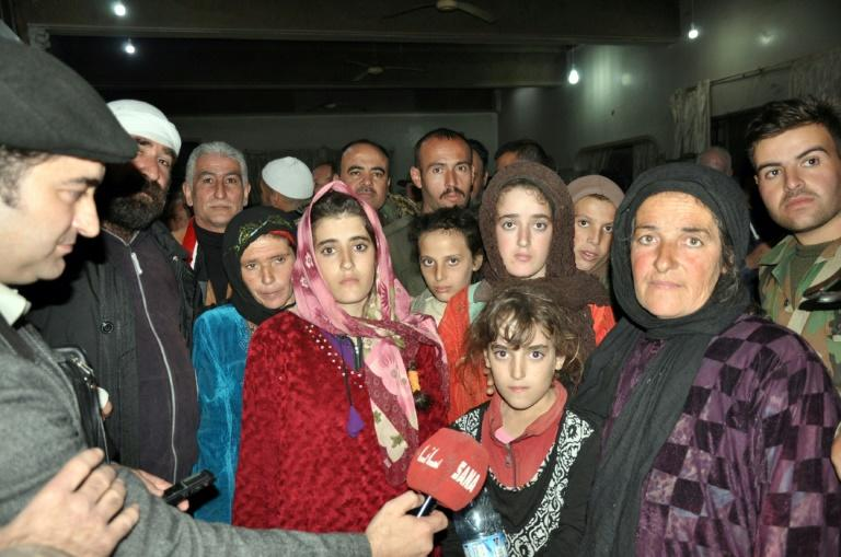 Syrian Druze women and children, freed from more than three months' captivity at the hands of the Islamic State group, are welcomed home by their families on November 9, 2018 are welcomed hom by their A handout picture released by the official Syrian Arab News Agency (SANA) on November 9, 2018 shows a group of Druze women and children, abducted in July from Sweida by the Islamic State group, pose for a picture as they are being welcomed by relatives upon their arrival overnight in their hometown in the southern Syrian province of Sweida