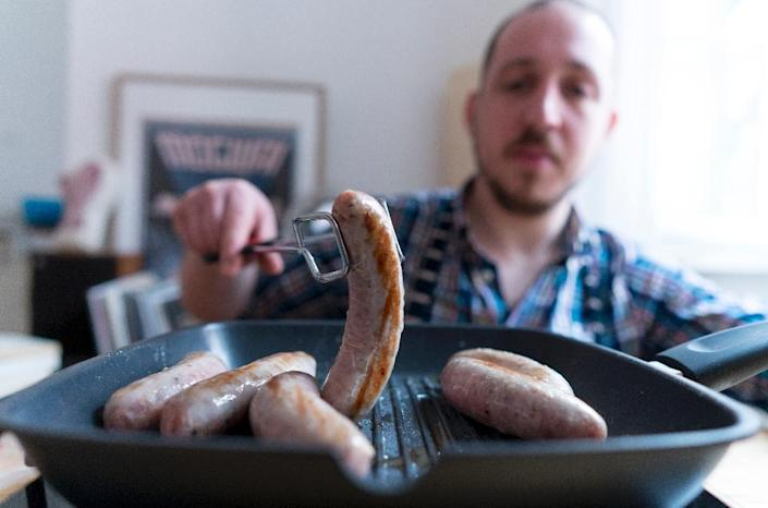 Richard Holmes grills his homemade British style sausages named 'Britwurst', at his Vienna apartment in the Austrian capital (AFP Photo/Joe Klamar)