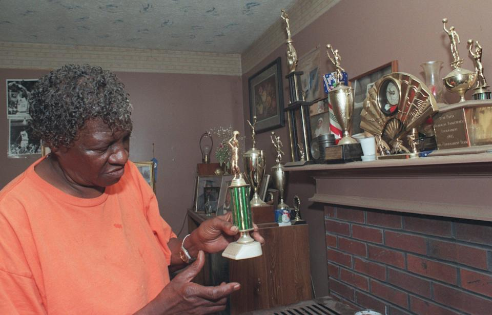 Sadie Wallace, mother of Pistons' Ben Wallace, looks at trophies awarded to her son during high school and college at her home in Hayneville, Alabama, March 21, 2002.