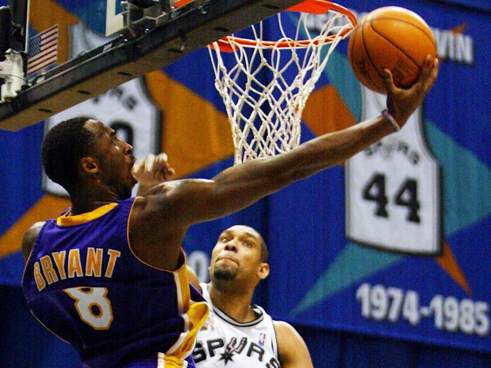 Kobe Bryant attempts a reverse layup against Spurs forward Tim Duncan during the 2002 playoffs.