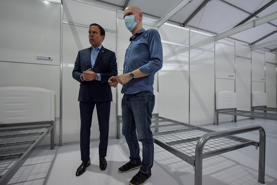 Sao Paulo state Governor Joao Doria (L) and Sao Paulo city Mayor Bruno Covas (R) visit a field hospital set up for coronavirus patients at Pacaembu stadium, in Sao Paulo, Brazil on March 27, 2020. - Brazil's top football clubs are handing over their stadiums to allow health authorities to turn them into field hospitals and clinics to fight the coronavirus pandemic. (Photo by NELSON ALMEIDA / AFP) (Photo by NELSON ALMEIDA/AFP via Getty Images)