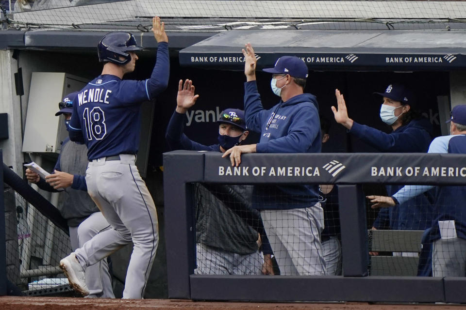 Tampa Bay Rays Joey Wendle (18) is greeted at the dugout after scoring on Yoshi Tsutsugo's RBI double during the seventh inning of a baseball game against the New York Yankees, Sunday, April 18, 2021, at Yankee Stadium in New York. (AP Photo/Kathy Willens)