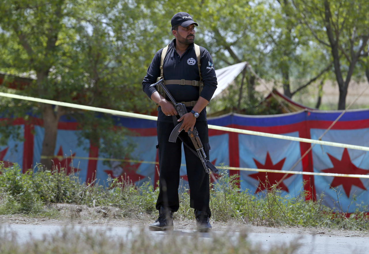 "A Pakistani police officer stands guard to cordon off the grave, rear, of Sana Cheema, an Italian woman of Pakistani origin, who was allegedly killed by her family members, in the neighborhood of Mangowal, near Gujrat, Pakistan, Wednesday, April 25, 2018. Pakistani police arrested the father and the uncle suspected in an ""honor"" killing of a 25-year-old Italian citizen, a woman of Pakistani origin who refused to marry the man they chose for her, a police officer said. (AP Photo/Anjum Naveed)"