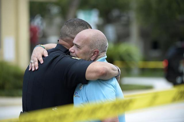 <p>Terry DeCarlo, executive director of the LGBT Center of Central Florida, right, is comforted by an Orlando Police officer after a shooting involving multiple fatalities at a nightclub in Orlando, Fla., June 12, 2016. (AP Photo/Phelan M. Ebenhack) </p>