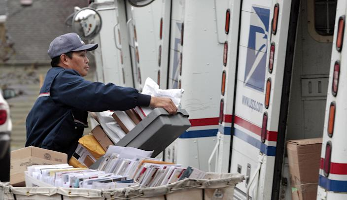 FILE - This Dec. 5, 2011 file photo shows letter carrier Diosdado Gabnat moving boxes of mail into his truck to begin delivery at a post office in Seattle. Americans for generations have come to depend on door-to-door mail delivery. It's about as American as apple pie. But with the Postal Service facing billions of dollars in annual losses, the long-cherished delivery service could be virtually phased-out by 2022 under a proposal a House panel was considering Wednesday. Curbside delivery, which includes deliveries to mailboxes at the end of driveways, and cluster box delivery would replace letter carriers slipping mail into front-door boxes. (AP Photo/Elaine Thompson, File)