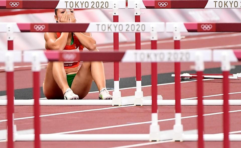 Luca Kozak sits on the track, holding her hands to her face.