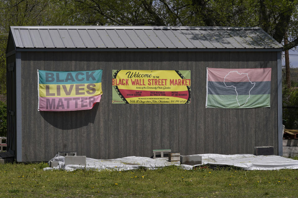 Flags hang on a shed at the Black Wall Street Market, Saturday, April 10, 2021, in Tulsa, Okla. The 6 miles between the old and new incarnations of Black Wall Street belie the dire connection that links them: Racial and socioeconomic inequality on Tulsa's north side has its roots in the 100-year-old atrocity of the Tulsa Race Massacre. (AP Photo/Sue Ogrocki)