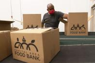 A volunteer pack boxes of food for distribution, at The Capital Area Food Bank, Tuesday, Oct. 5, 2021, in Washington. (AP Photo/Jacquelyn Martin)