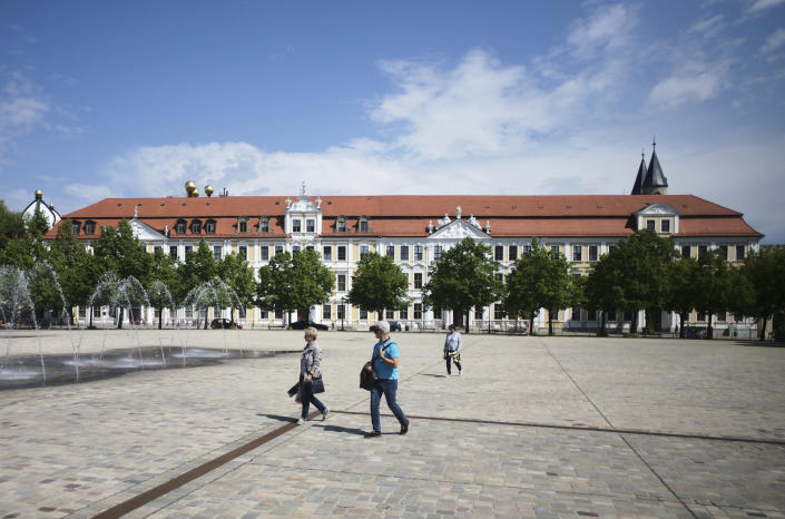 People walk on the square in front of German federal state Saxony-Anhalt parliament building in Magdeburg, Germany, Wednesday, June 2, 2021. The state vote on Sunday, June 6, 2021 is German politicians' last major test at the ballot box before the national election in September that will determine who succeeds Chancellor Angela Merkel. (AP Photo/Markus Schreiber)