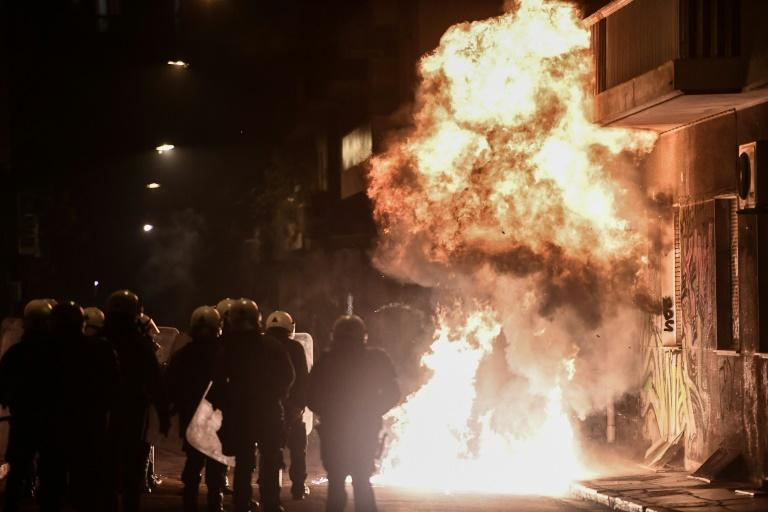 Flames from petrol bombs burn after exploding close to anti-riot police officers in downtown Athens on at demonstrations on the 10th anniversary of the fatal shooting of a teenager which sparked major riots in Greece in 2008