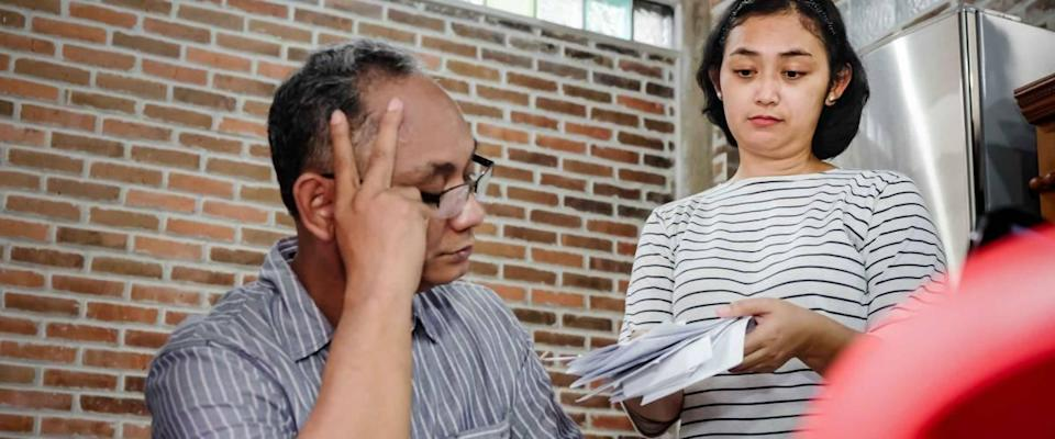 Woman handing husband sitting at table a pile of bills, both look stressed.