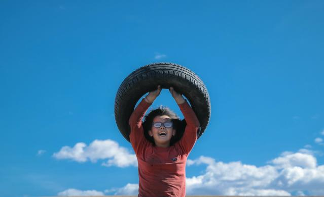 In this photo taken on Sunday, March 10, 2019, a little girl laughs lifting a tire before a ritual marking the upcoming Clean Monday, the beginning of the Great Lent, 40 days ahead of Orthodox Easter, on the hills surrounding the village of Poplaca, in central Romania's Transylvania region. Romanian villagers burn piles of used tires then spin them in the Transylvanian hills in a ritual they believe will ward off evil spirits as they begin a period of 40 days of abstention, when Orthodox Christians cut out meat, fish, eggs, and dairy. (AP Photo/Vadim Ghirda)