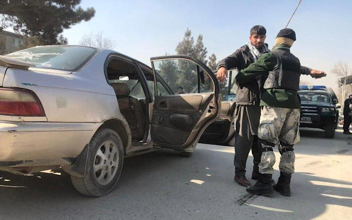 Afghan security officials check vehicles at a checkpoint in Kabul, Afghanistan, - Shutterstock/Shutterstock