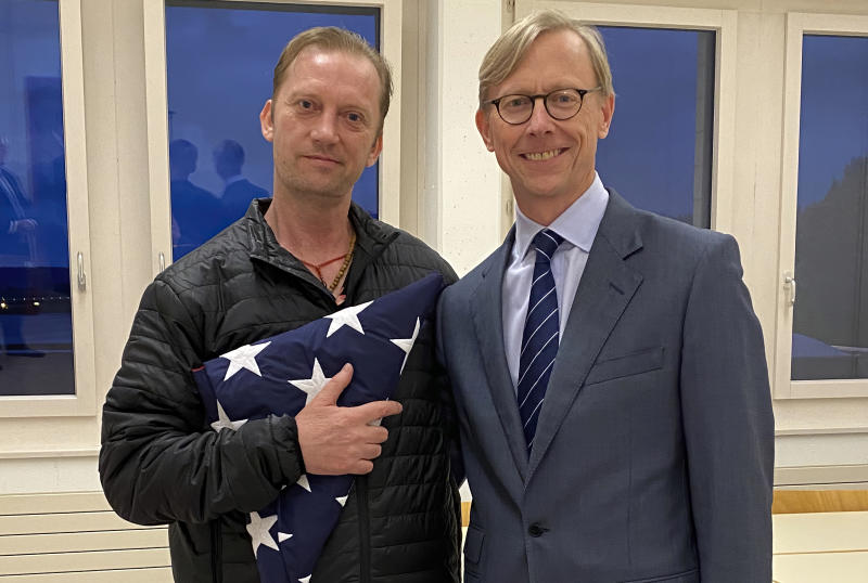In this image provided by the U.S. State Department, Michael White holds an American flag as he poses for a photo Thursday, June 4, 2020, with U.S. special envoy for Iran Brian Hook at the Zurich, Switzerland, airport after White's release from Iran.  White, a Navy veteran who's been detained in Iran for nearly two years has been released and is making his way home, with the first leg on a Swiss government aircraft. (U.S. State Department via AP)