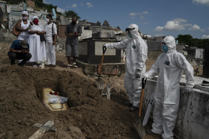 """Taina dos Santos, third from left, attends the burial of her mother Ana Maria, a 56-year-old nursing assistant who died from the new coronavirus, in Rio de Janeiro, Brazil, Tuesday, April 28, 2020. Dos Santos said that the situation in the Salgado Filho public hospital where her mother worked is complicated and that some health workers have to buy their own protective gear. """"She gave everything to her job until the very end,"""" said the 27-year-old daughter. (AP Photo/Leo Correa)"""