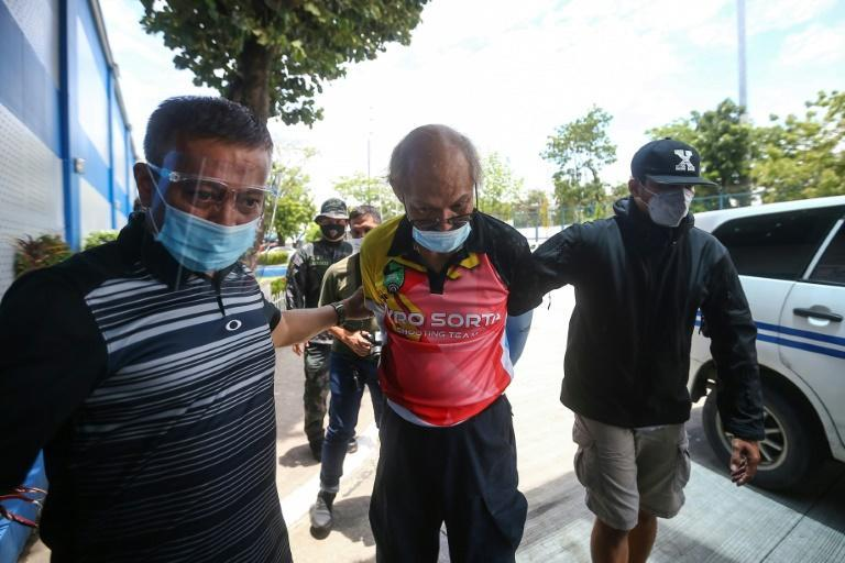 Ruben Ecleo is escorted by officers outside police regional headquarters in Manila, following his arrest