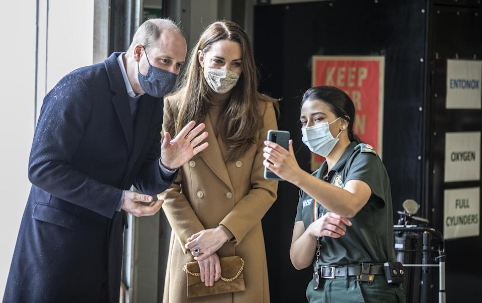 The Duke and Duchess of Cambridge, during a visit to Newham ambulance station in East London, talk with the family of paramedic Jahrin (Jay) Khan via a mobile phone. The family is in London but her father joined the conversation from Bangladesh. Ms Khan has been unable to see her family through the pandemic. Picture date: Thursday March 18, 2021.
