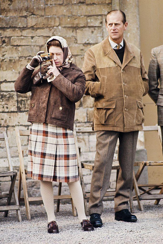 <p>A plaid skirt, jacket and head scarf is Queen Elizabeth II's go-to casual outfit. Here she is in 1973 with her husband Prince Philip at the Badminton Horse Trials.</p>