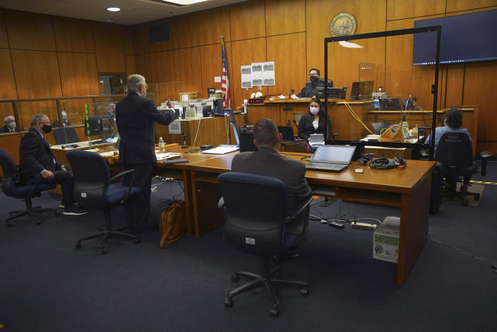 Defense attorney Dick DeGuerin, center standing, addresses Judge Mark Windham, center in back, alongside fellow defense attorney David Z. Chesnoff, left, and Deputy District Attorney John Lewin, at right, representing the prosecution, during the murder trial of Robert Durst Monday, May 17, 2021, in Inglewood, Calif. The murder trial of the multimillionaire has resumed in Los Angeles County after a 14-month recess without the defendant present and with arguments about whether the case should continue at all. (Al Seib/Los Angeles Times via AP, Pool)