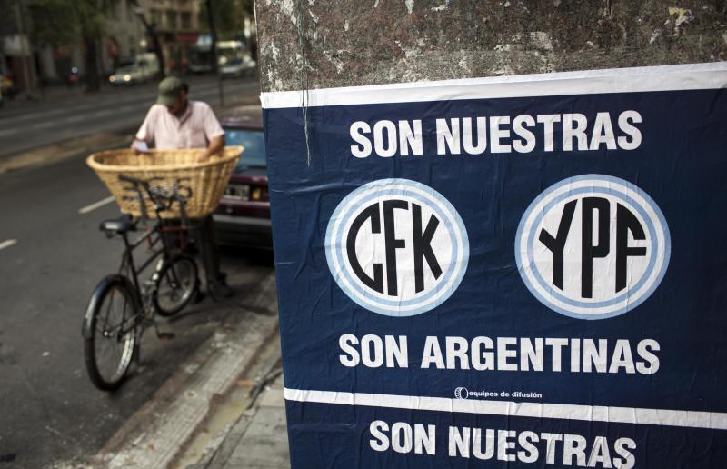 "A sign reading in Spanish ""They are ours. CFK. YPF. They are Argentine"" hangs in Buenos Aires, Argentina, Tuesday April 17, 2012. President Cristina Fernandez pushed forward a bill to renationalize the country's largest oil company on Monday despite fierce criticism from abroad and the risk of a major rift with Spain. Fernandez said the legislation put to congress would give Argentina a majority stake in oil and gas company YPF by taking control of 51 percent of its shares currently held by Spain's Repsol. (AP Photo/Natacha Pisarenko)"