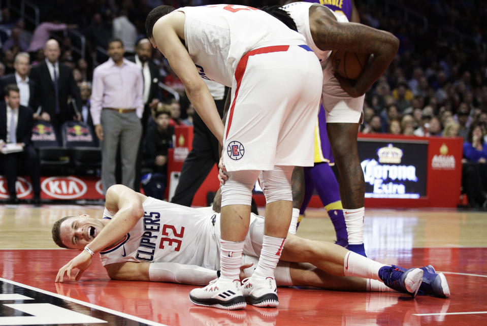 Blake Griffin grimaces in pain after the collision with Austin Rivers that injured his knee. (AP)