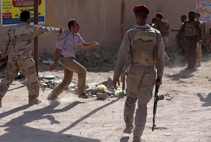 Iraqi security forces detain a supporter of Shiite Sheikh Mahmud al-Hassani al-Sarkhi, following clashes in the shrine city of Karbala on July 2, 2014 (AFP Photo/Mohammed Sawaf)